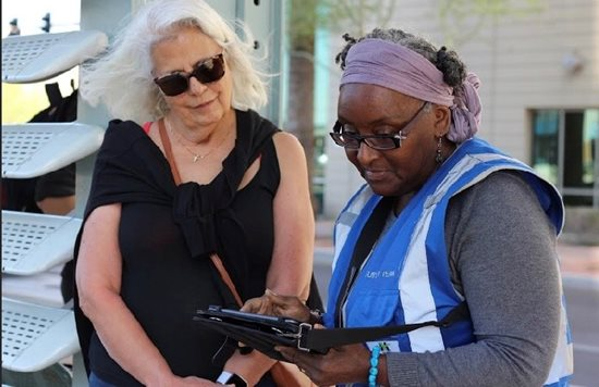 Two women reviewing a survey in a suburban area.