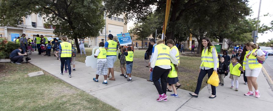 Adluts and kids walking together for Walk to School Day