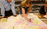 A woman pointing to a location on a large map