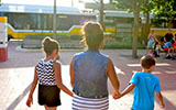 Image of A woman walking a girl and boy to the bus